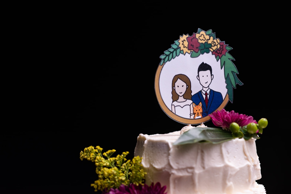 A delicious white wedding cake topped by a portrait of the bride and groom from one of our weddings is shown.