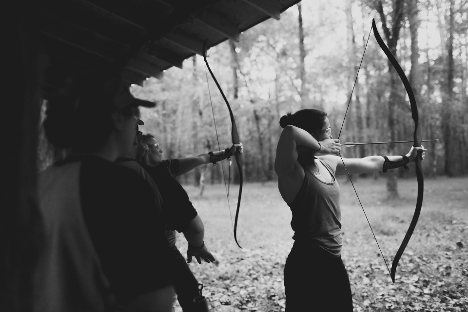 Two archers aiming bows on archery range during wedding activities