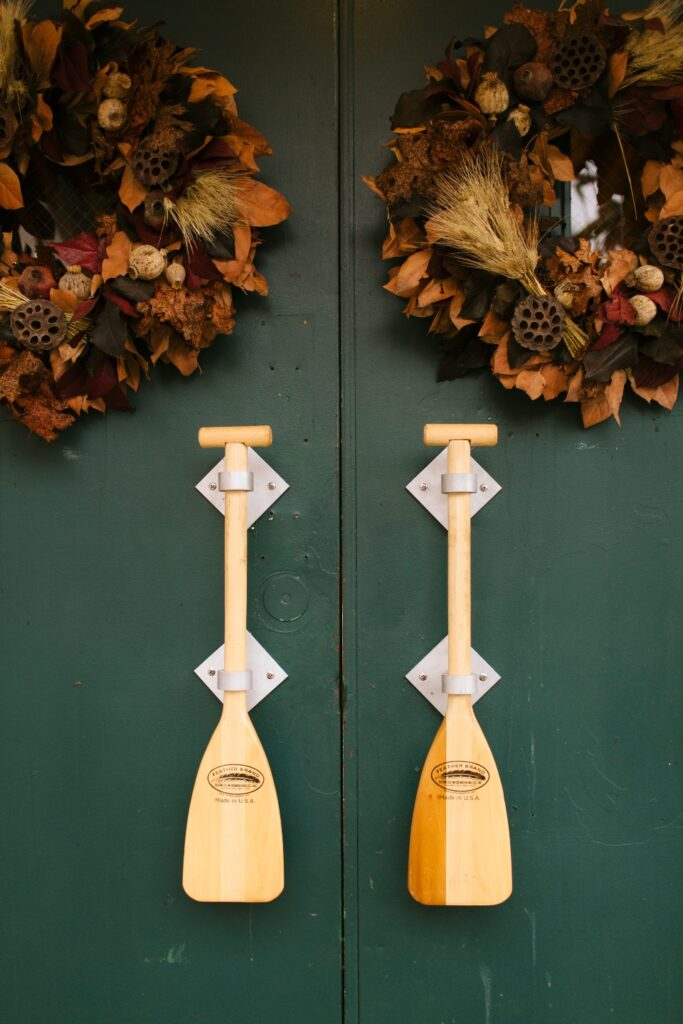 A close up image of the entrance to our dining hall. A dark camp green with canoe oars as handles.