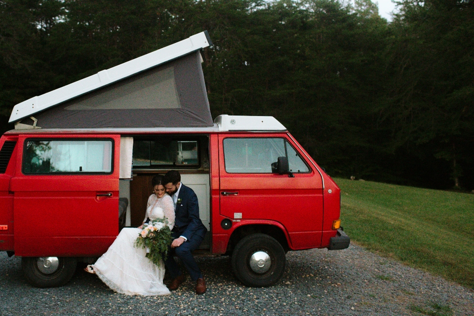 A Bride and Groom sitting in a parked red volkswagen van