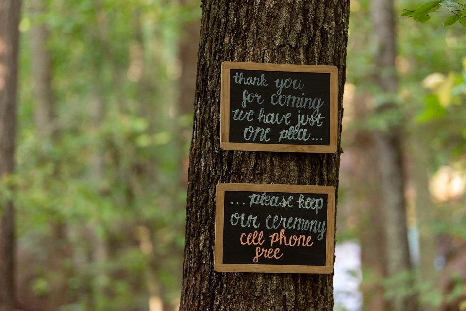 Chalkboard signs give directions and instructions to a wedding party that the ceremony will be cell phone free.