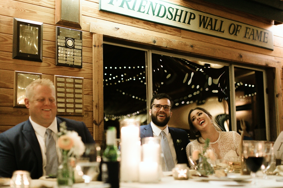 The head table of the wedding is decorated with candles and flowers. The bride and groom laugh as they sit in front of the Camp Friendship Wall of Fame.