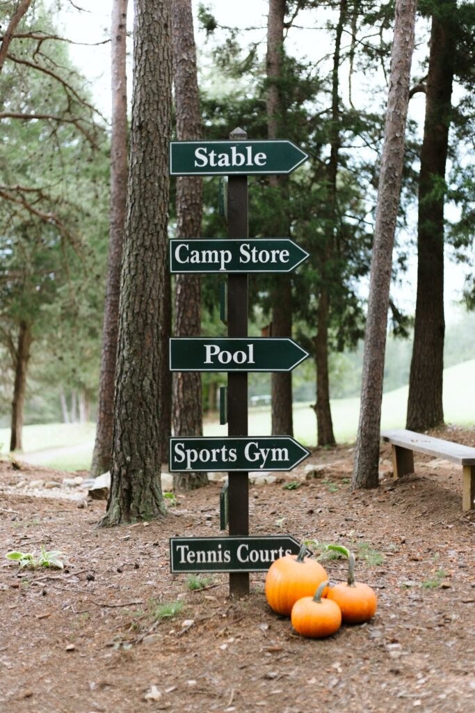 "Directional sign with the following words ""Stable"", ""Camp Store"", ""Pool"", ""Sports Gym"", and ""Tennis Courts"""