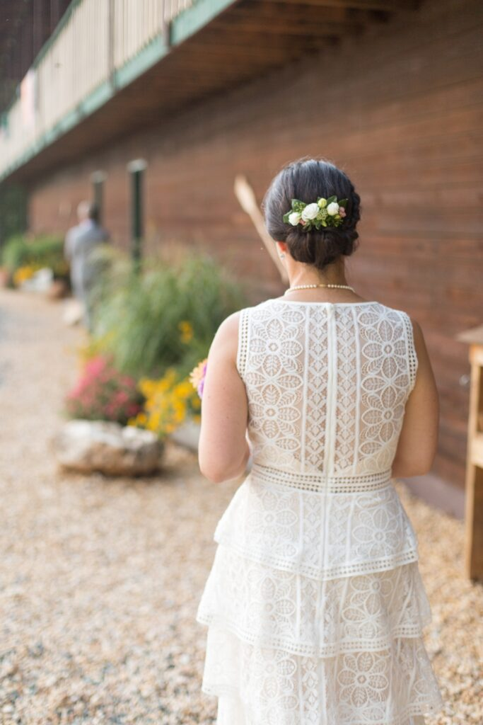 A bride faces her back to the camera as she walks past the decroative landscaping in front of our overlook lodge, an option for our Virginia wedding venue.