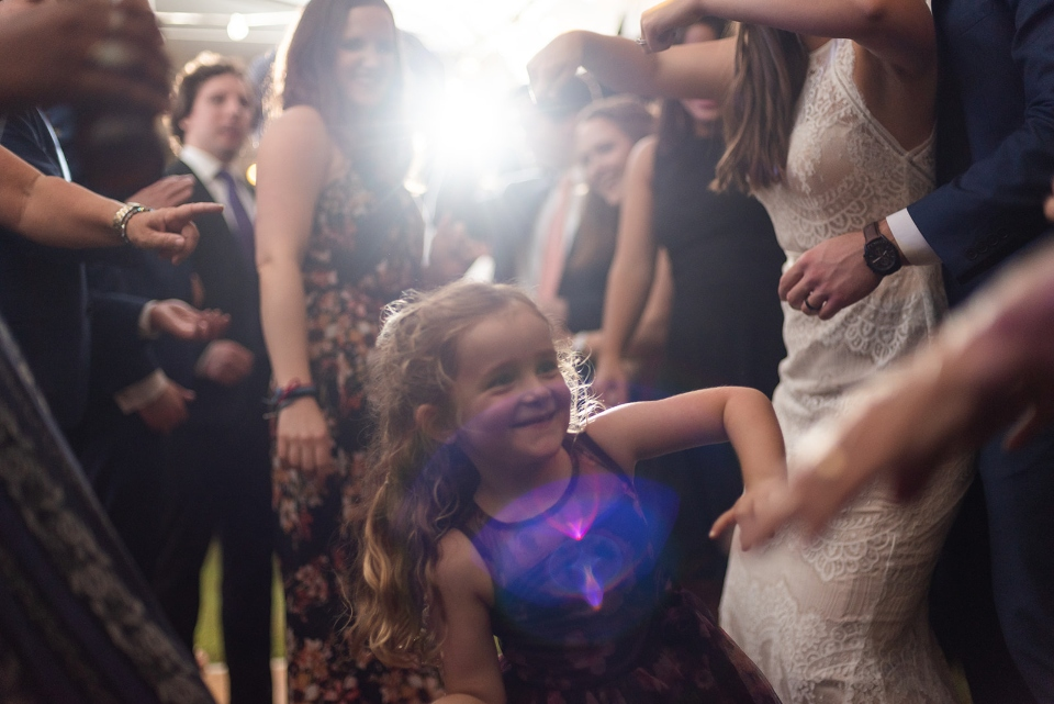 A young girl dances with family in the middle of the post camp wedding reception.