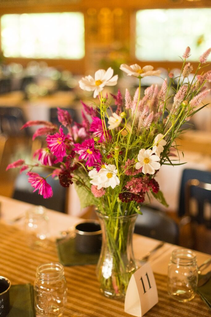 A decorative floral arrangement takes the place of a centerpiece in one of our wedding venue dining hall arrangements.