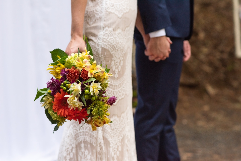 The holding hands of a bride and groom are shown as the bride holds her bouquet after her wedding.