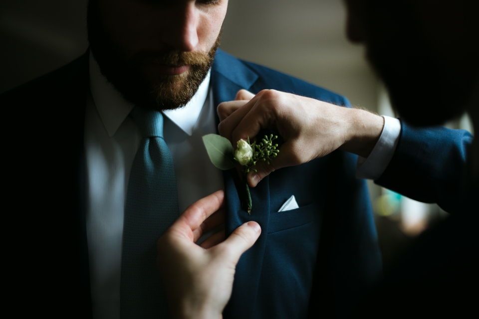 A boutonniere is pinned to the navy jacket of a groomsman.
