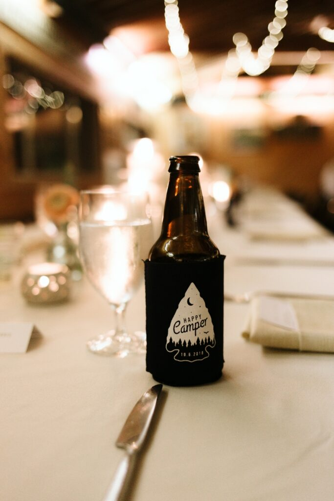 A bottle of beer with a camp beer cozy sits on a decorated camp table set with a white table cloth for the wedding.