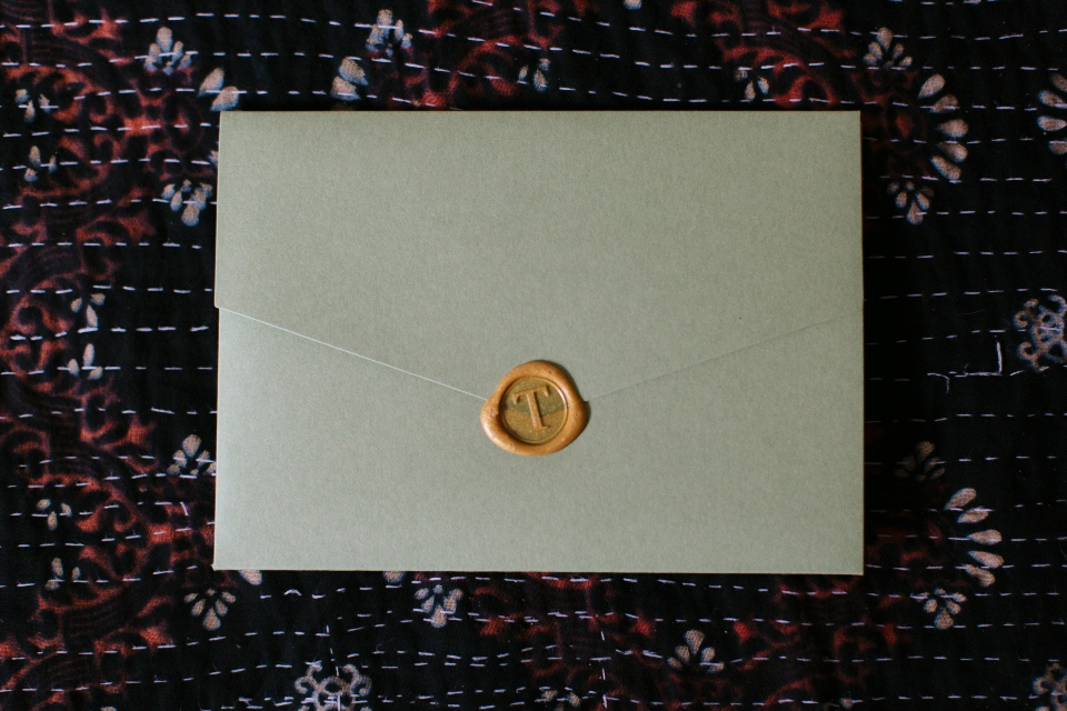 a sealed wedding invitation, sealed with gold wax.