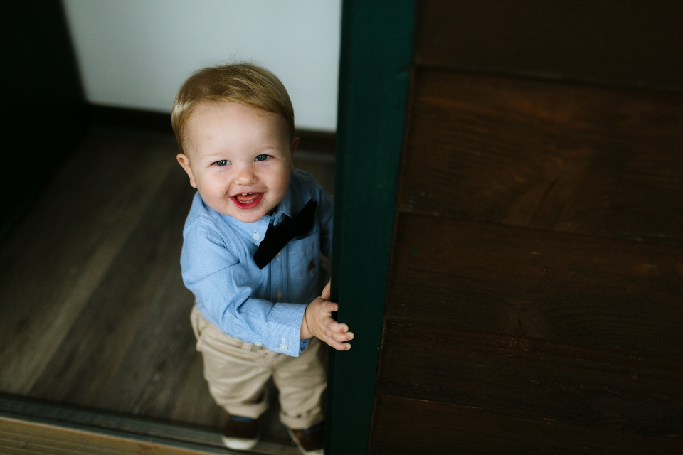 A young child in dress clothes and a bow tie smiles with joy as he gets ready for the wedding.