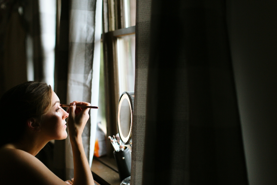 A bride applies her make up as she gets ready for her summer camp wedding.