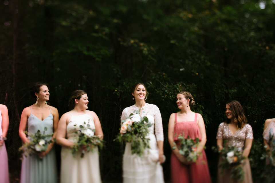 A bride and her brides maids pose in front of the woods of our natural Virginia wedding venue.