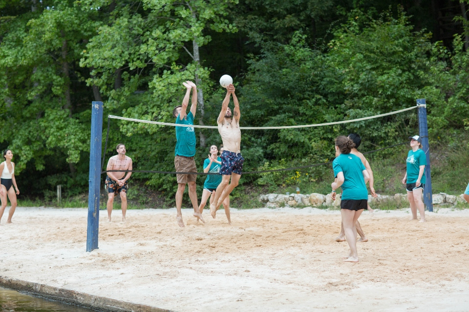 Two men get ready to spike a volleyball during a game of beach volleyball on the shore of Friendship Lake
