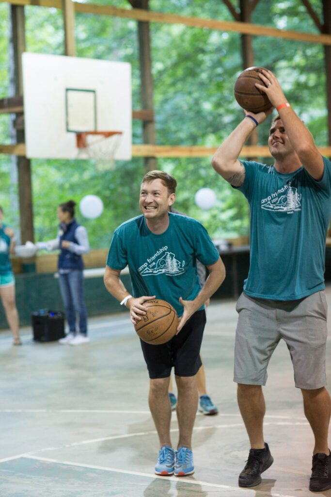 Two men shooting basketballs at the gym at Camp Friendship