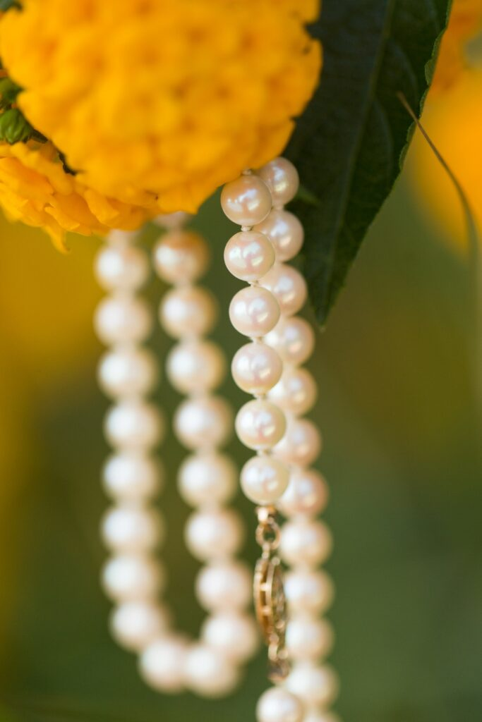 A close up of a bride's pearls hanging from the flowers of her bouquet.