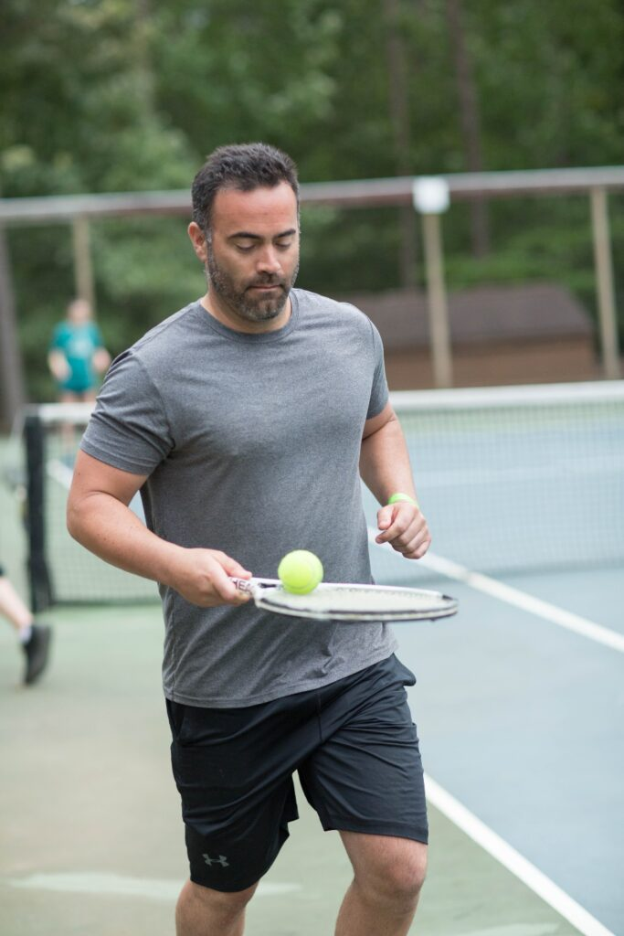 Man balancing tennis ball on racket at tennis summer camp courts