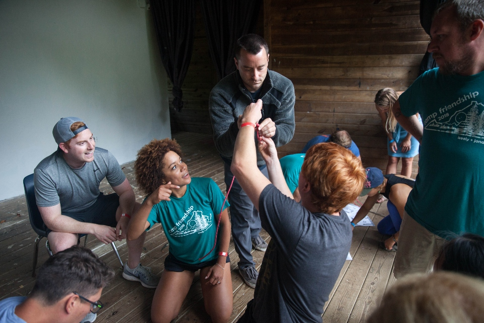 Male staff teaching knot tying as part of a race at summer camp wedding