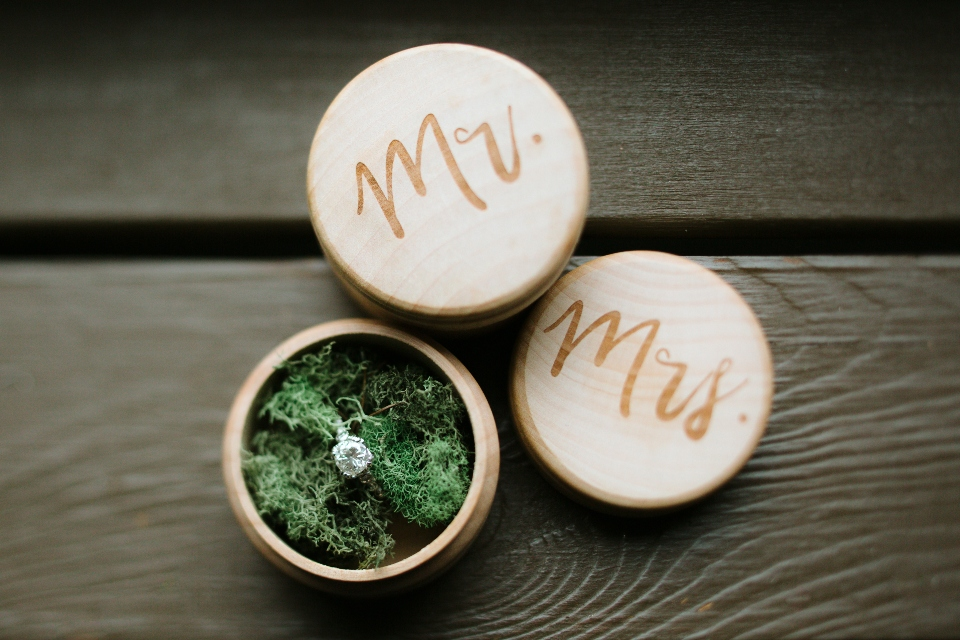 A wedding ring is displayed in a wood box with fake grass to give an outdoor camp vibe.