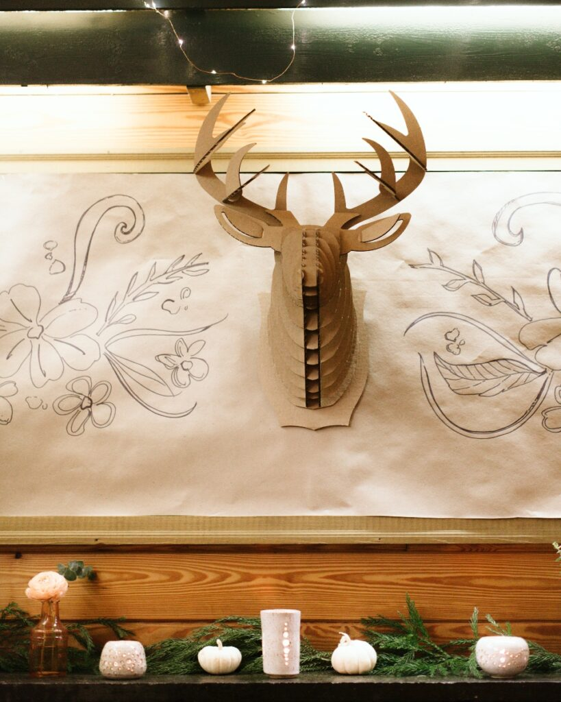 Decorations, including a cardboard constructed deers head and candles adorn a mantle for one of our summer camp weddings.