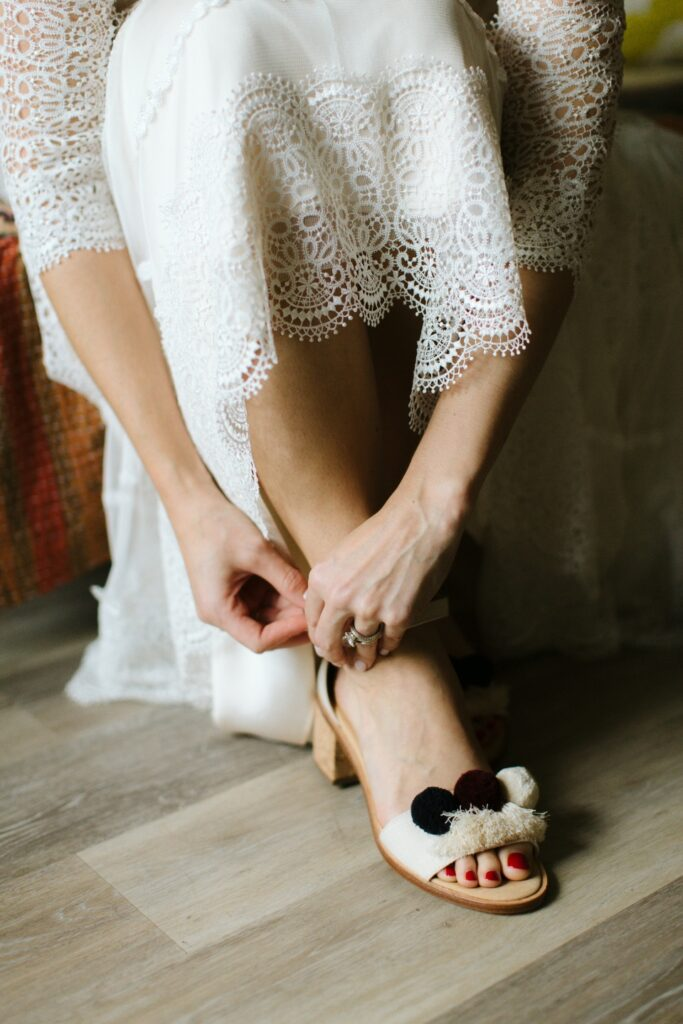 A bride puts on her sandal in preparation for the ceremony.