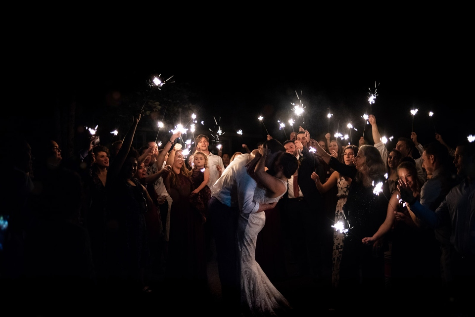 A wedding party celebrates the night with sparklers and smiles in one of our summer camp villages.