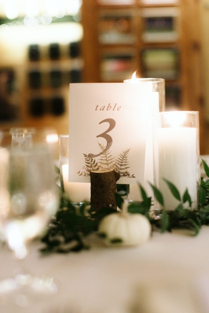 A tasteful candle center piece and table number decorate one of our camp wedding meal layouts.