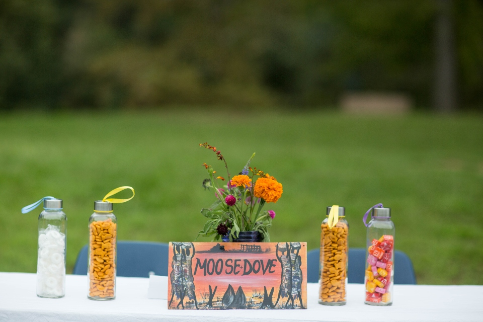 Clear bottles containing snacks like goldfish are displayed on a gifts table for our Virginia wedding venue.
