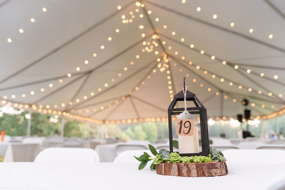 A wedding tent strung with lights is shown, a beautiful camp wedding venue atop our mountain boarding hill.
