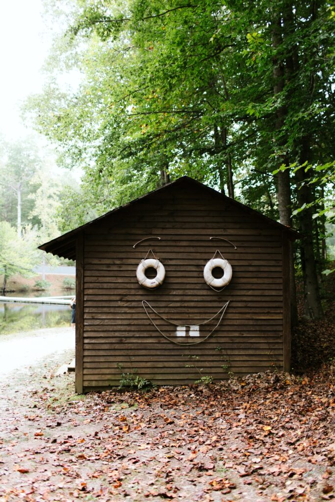 Sid the shed smiles next to camp friendship lake. He contains all of our boating supplies.