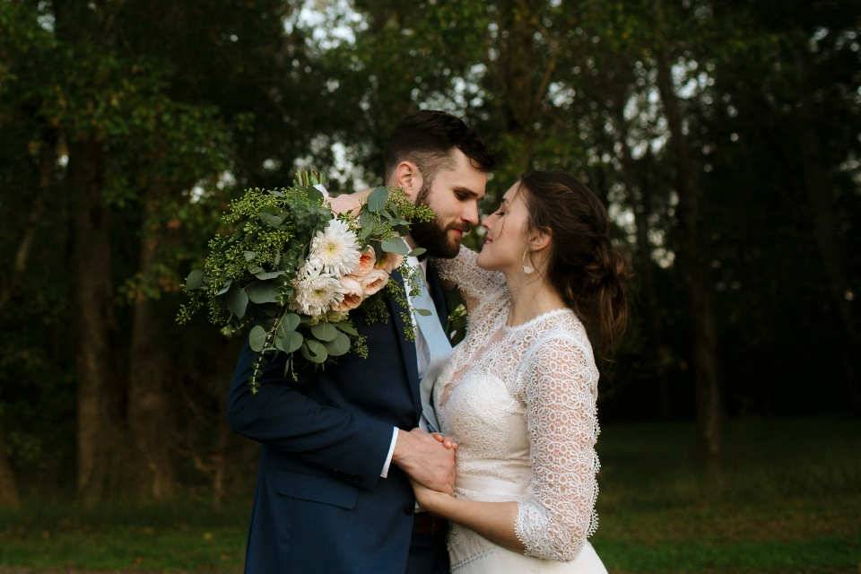 Bride and Groom hold each other with beautiful bouquet