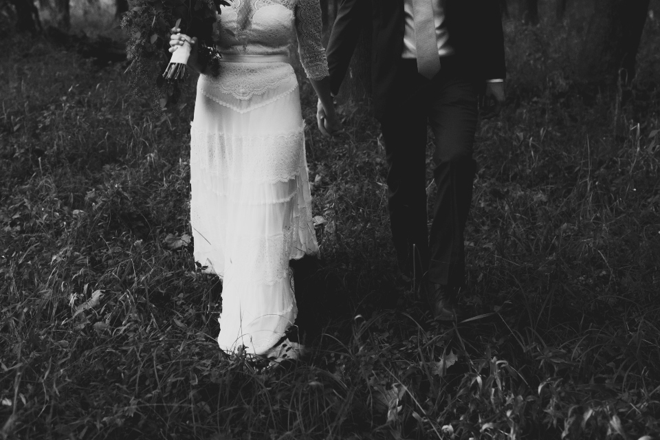 Bride and Groom walking hand-in-hand through the wilderness at their outdoor virginia wedding