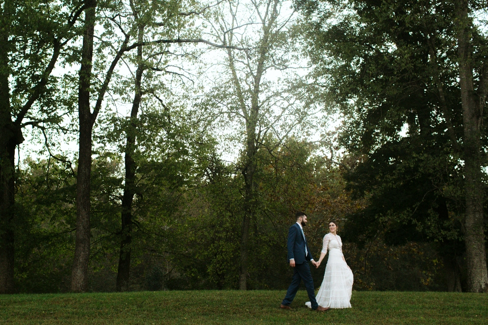 Bride and Groom walk hand in hand on green grass with green trees in the background