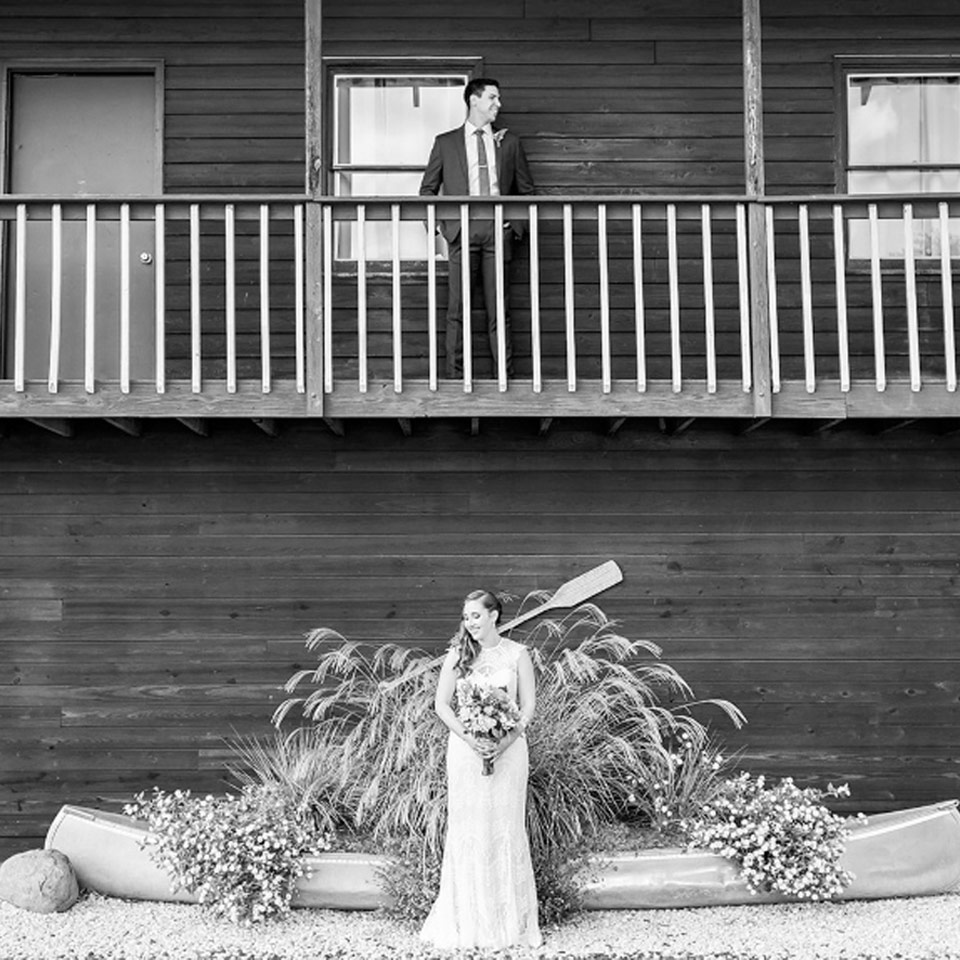 Groom standing on second floor balcony and bride standing below waiting to have their first look at Virginia wedding venue
