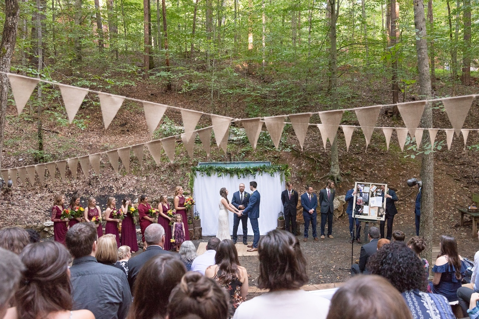Summer Camp wedding with bride, groom, bridesmaids, groomsmen, and crowd watching the ceremony with bunting hanging above.