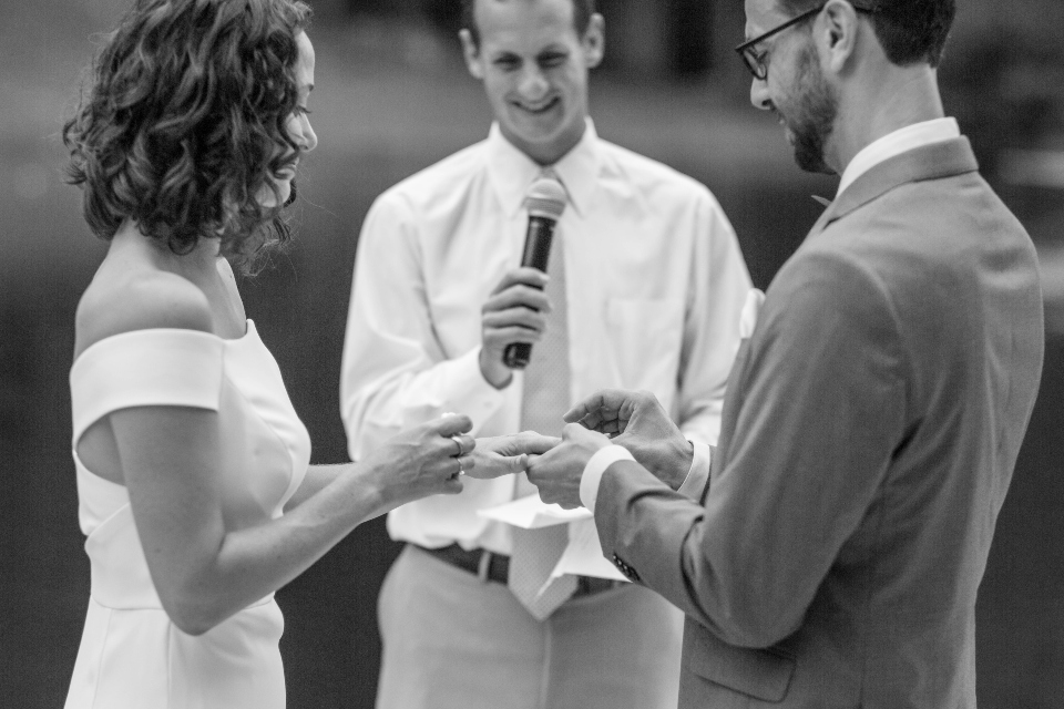 Groom places wedding band on bride's finger with officiate looking on.