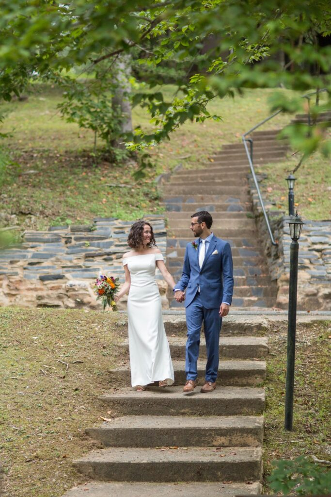 Bride and Groom walking down stone stairs hand in hand