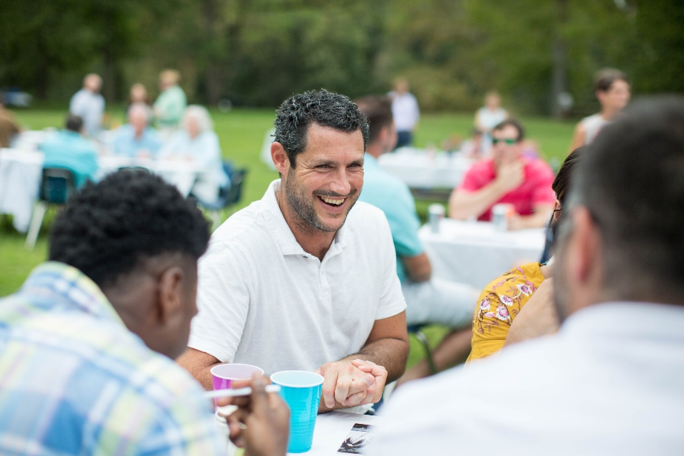 Men enjoying food and conversation during outdoor Wedding Reception meal