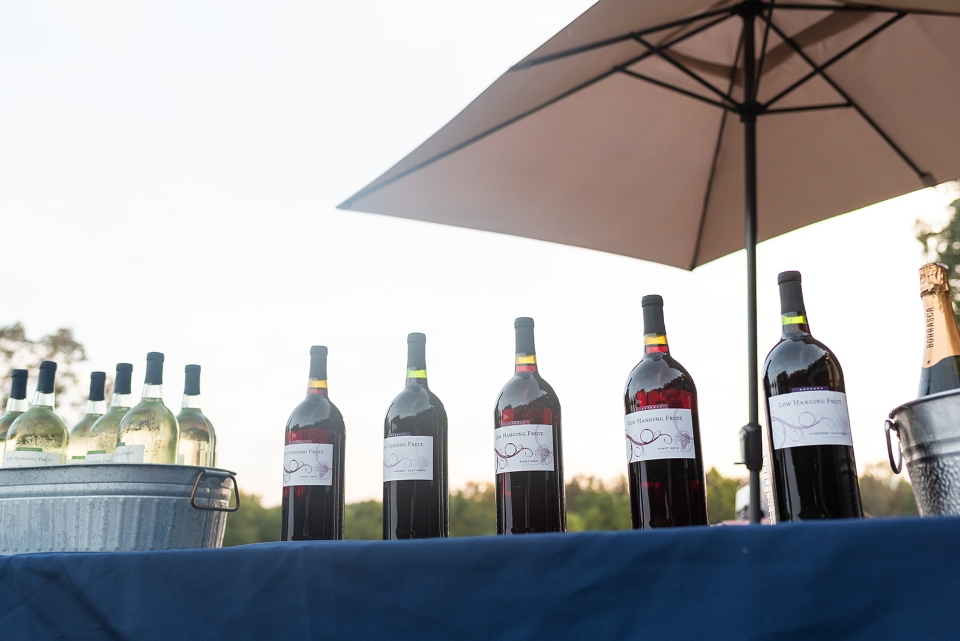 Bottles of wine sitting on a table with an outdoor umbrella at virginia wedding venue