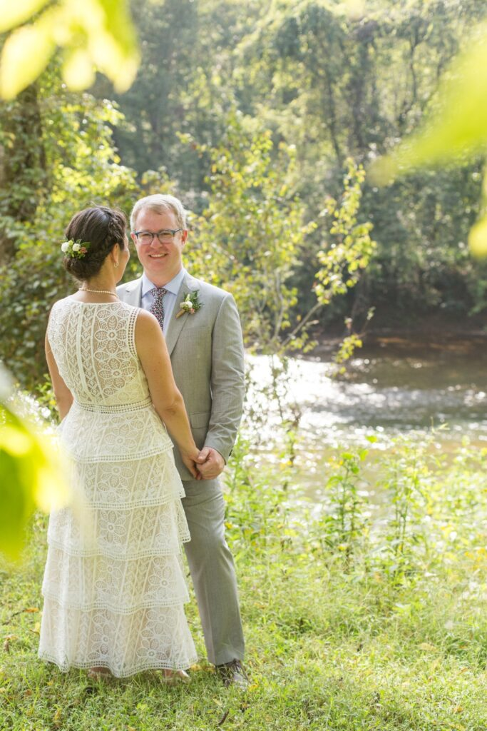 Bride and Groom holding hands in greenery next to Rivanna river at Virginia summer camp wedding