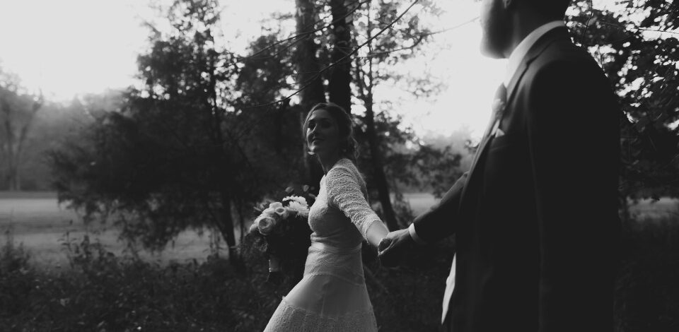 Bride holding grooms hand; leading him through the woods at Virginia Wedding venue