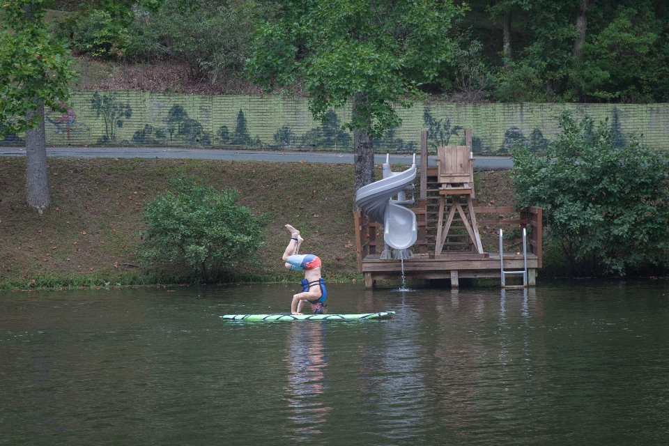 Man in a handstand position doing yoga on a paddle board in Friendship lake