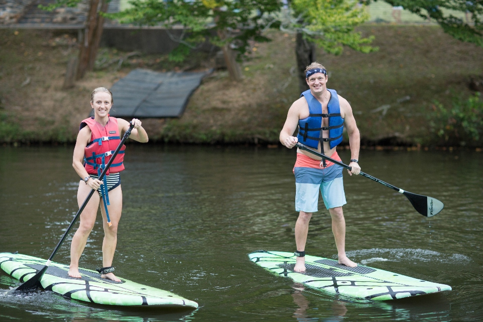 Man and Woman paddle boarding on the lake at Camp Friendship wedding venue
