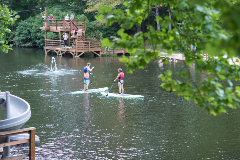 Two people paddle boarding on the lake at Camp Friendship
