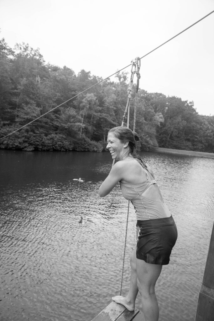 Woman getting ready to zipline into lake at Camp Friendship