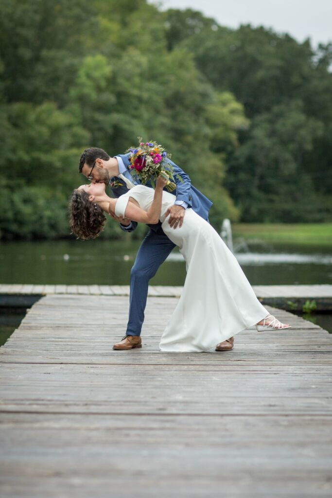 Groom dips bride and kisses her on the dock on the lake at Camp Friendship