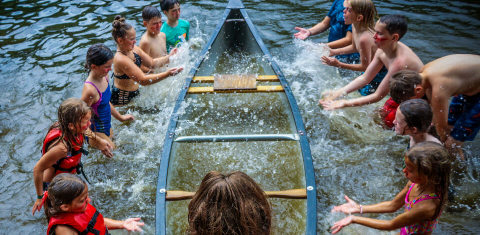 Campers splashing water into a canoe during a Color Wars event