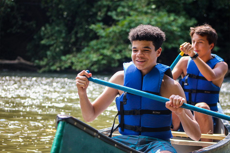Teen boy campers canoeing at Camp Friendship in Virginia