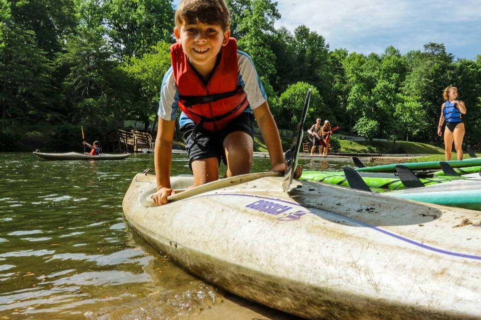 Young boy camper gets ready to kayak at overnight camp in Virginia