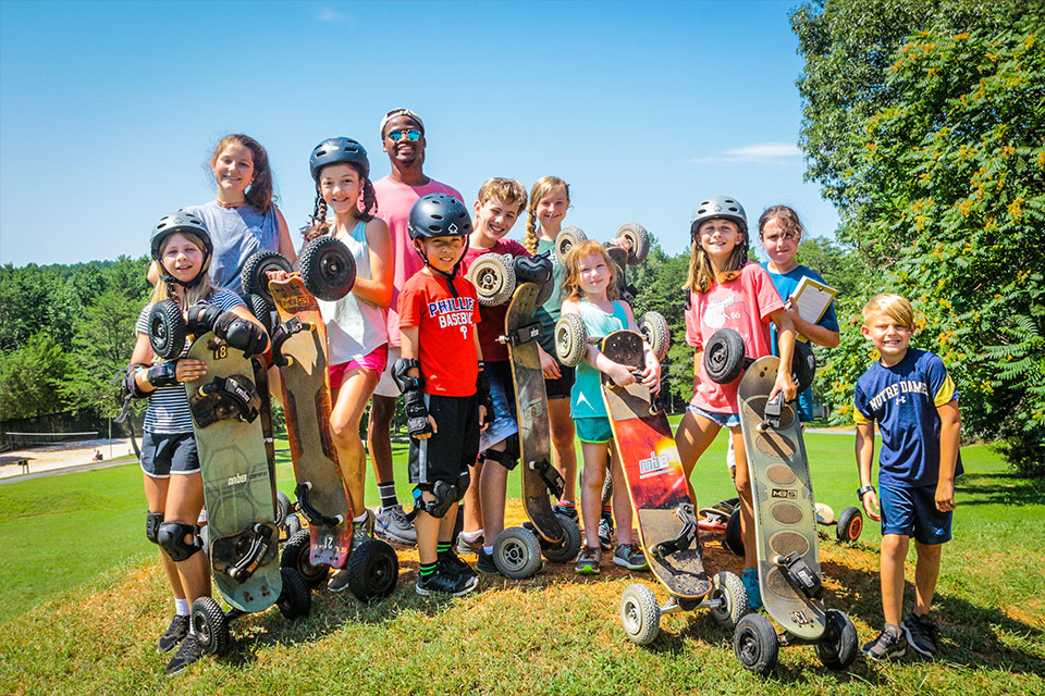 Campers and Counselors getting ready to mountain board down the mountain boarding hill at Camp Friendship